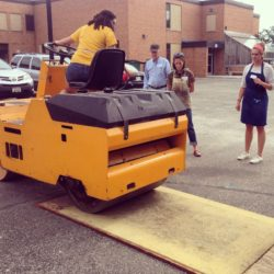 A woman backs a yellow streetroller over a board.